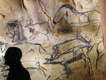epa04695270 A visitor looks at cave art depicting animals in the 'caverne du pont d'arc', the Chauvet's cave replica, near Vallon-Pont-D'arc, Southern France, 08 April 2015. The cave is the biggest replica cave in the world, it contains 1000 drawings, with 425 animals figures, 27 original paintings and around 450 bones. The cave will open for the public on 25 April 2015.  EPA/GUILLAUME HORCAJUELO